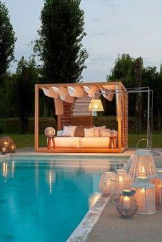 jardim com piscina com pergolado e luminárias ao redor