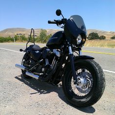 Black Sportster 48 with small headlight fairing, replace with gloss one? sissy bar in back looks nice, heat wrap pipes in midnight grey, get fat back tire