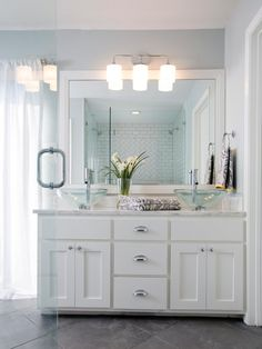 Joanna brightened up the space with white stone countertops, a dual vanity and glass vessel sinks, spacious stand-up shower and updated lighting.