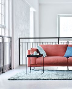 coral red linen sofa | industrial style open plan loft with huge windows | IKEA Nockeby sofa with a Bemz cover in Coral Brera Lino by Designers guild | Blue Bemz linen cushion covers | industrial blacony railings