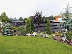 Po pravé straně od vstupu do domu lemují plot kosterní stromy, keře, trvalky a letničky pokryté mulčovací kůrou.