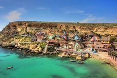 Bienvenue dans un lieu pictural, un havre de paix composé de mignonnes petites maisons en bois, où les épinards pousse très vite et où les bateaux sont ancrés en toute sécurité. Le Village de Sweethaven se trouve à Malte, dans la mer Méditerranée, et a été construit comme décor pour le film Popeye l