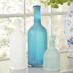 Maderia Bottles | Reminiscent of sea glass found on the shore, these three glass bottles are beautifully hand-blown in frosted shades of blue and white.