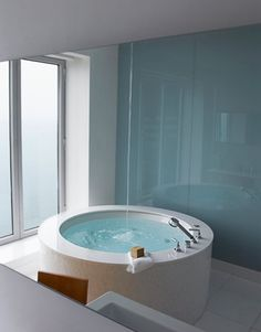 "Back-painted blue glass reflects a bath, high in a Chicago tower, created expressly for a woman. ""It's the ultimate spa experience,"" says designer Michael Richman. Water streams from a splash-free Kohler ceiling-mount bath filler into her Americh Japanese soaking tub."