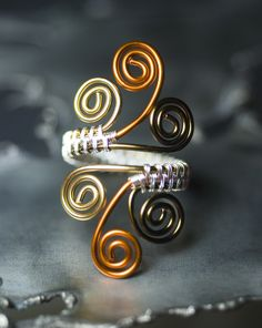 In this elegant quad tone ring design, intricate wire weaving is the centerpiece with silver tinted copper wire contrasting with a bronze, copper, and gold tinted copper wrapped spiral ring frame.  My Etsy shop: www.mossandmist.etsy.com