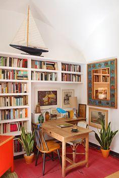 Área de trabajo - AD España, © Asier Rua La casa de pueblo más bonita Sobre la estantería repleta de libros, maqueta de barco de los 60. El espejo cerámico es de Muel, España y la alfombra antigua es jordana. Foto Asier Rua