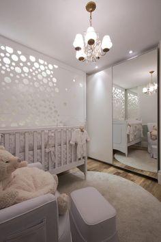 Quarto de bebê com lustre e espelho para aumentar a ambiente.