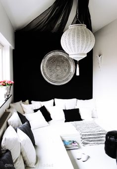 Chic simple Moroccan lounge area with banquettes in charcoal & white. The lantern is tin & painted white. Melanie el Haddad