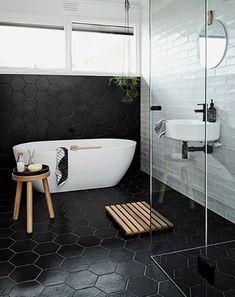 Cuarto de baño con alicatado en azulejo negro en pared principal y suelo, con bañera y lavabo.