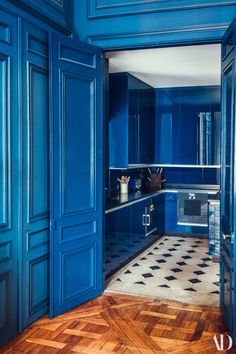 Pierre Sauvage of is not afraid of color. In his Paris apartment, shades of blue dominate the walls, especially in the kitchen where high-gloss blue-painted cabinetry intersects with the Pierre de Bourgogne–and–black Belgian marble floor.