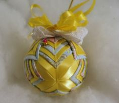 "Precious Moments handmade quilted ornament:  This 3"" handmade quilted ornament is made with the new cathedral pattern was made of yellow satin ribbon with precious moments fabric. The side and top of the ornament is wrapped in white lace and yellow satin ribbon. This ornament would look charming in your favorite bowl or basket or as a decoration in a room. It will make a great Christmas tree decoration! It makes a great gift for family, friends, or teachers.  These ornaments are made by hand ..."
