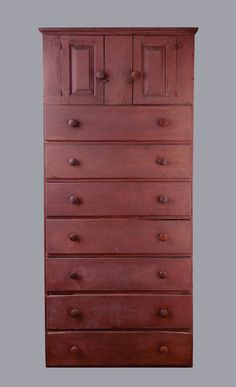 "McCue Shaker CatalogCUPBOARD OVER DRAWERS  Pine, original red/purple painted finish, two door cupboard top with raised panel doors over seven dovetailed and lipped drawers, ""Purchased from Andrews who says 'original purplish paint: A very early example of this type of chest, from the Church family in Hancock, (c. 1800, possibly earlier).   SOLD 21,060$"