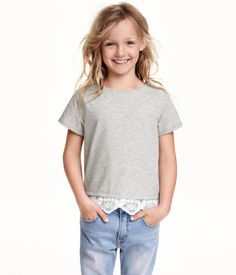 Cropped top in jersey with short sleeves and a lace trim at the hem.