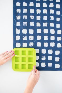 Use an ice cube mold to create a pattern on paper with paint.