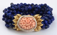 LAPIS BEAD, CORAL AND DIAMOND BRACELET, DAVID WEBB.  With carved lapis beads and 18k gold clasp with 1.50 carats of diamonds and a floral carved pink coral, signed 'Webb, 18kt, Plat'.  (=)