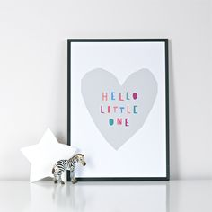 Hello Little One Print- GREY. This gorgeous print is perfect for a modern nursery or child's room, or as a new baby gift. Beautiful coloured letters on a simple cut-out style grey heart shape make this a stylish, contemporary and cute print which has a sweet and happy message.Print of an original image by Ingrid Petrie. Image © Ingrid PetrieSize: A4 and A3 sizes available. Materials: image is printed on quality 300gsm uncoated card which is FSC certified.Plea...