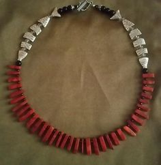 Red coral necklace:  Rust sponge coral sticks with silver tone fish on sides and black onyx beads.