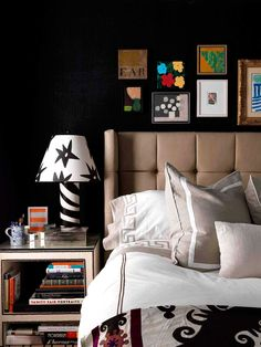 Black bedroom walls, small gallery wall, and neutral bed and bedding