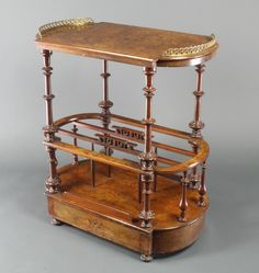 """Lot 1213, A Victorian oval and inlaid figured walnut Canterbury, the upper section with crescent shaped brass gallery, the base fitted 3 divisions and drawer to the base 29""""h x 26 1/2""""w x 15 1/2""""d, est  £100-150"""