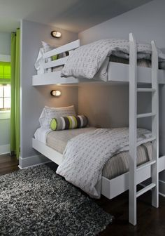 Fun modern boys' bedroom with gray walls paint color, white floating twin beds, white ladder, gray wool rug, gray green yellow black bolster pillows and green curtains window panels.