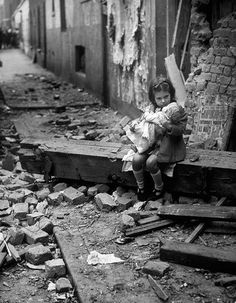 A little girl holding her doll in the rubble of her bomb damaged home.