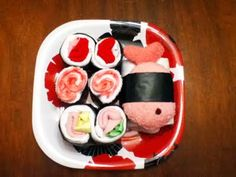 Sushi made out of all things baby, that is, like hair bows, tiny socks, and wee wash cloths. That cute fish plushie is a nice touch too.