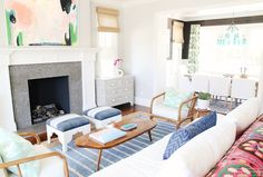 White living room with light blue rug, stools, and pillows with great big fireplace