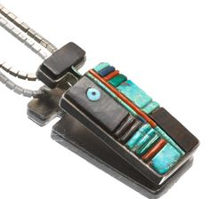 A Hopi pendant Charles Loloma, a stylized figural representation, set in a mosaic pattern of ironwood, turquoise, coral, malachite and lapis lazuli in a silver frame. length 2 3/8in