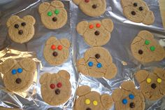 Bear shaped cookies using peanut butter cookie dough, M&M's for the eyes and a chocolate chip for the nose, rolling a big ball for the head, smashing it down lightly with the bottom of a cup and then rolling two little balls for each of the ears! #Teddy_Bear_Recipes