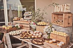 Cupcake arrangements on a variety of different stands were p Cookie Table Wedding, Wedding Buffet Food, Candy Bar Wedding, Wedding Desserts, Picnic Table Wedding, Rustic Buffet, Rustic Food Display, Rustic Candy Bar, Cupcake Arrangements