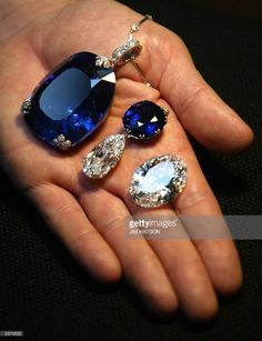 A man holds a 478 carat sapphire (L) which was previously owned by Queen Marie…