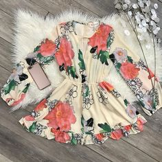 Stand out in this floral, colorful romper! It has a v-neckline that wraps around to the elastic waist. It has long sleeves with an elastic hem to give that perfect fit. The back zips up a quarter of t
