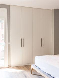 Las puertas del armario empotrado del dormitorio están lacadas en blanco, los tiradores de madera destacan sobre las puertas.
