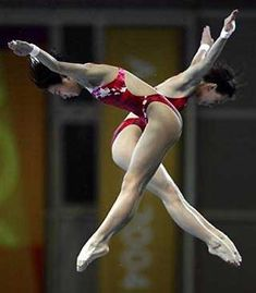 China's Lao Lishi (front) and Li Ting dive to the gold medal in the Women's 10 meter synchronized platform diving event at the 2004 Olympic Games in Athens,