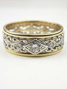 Vintage Two Toned Diamond Wedding Ring  In this vintage diamond wedding ring, a pierced scroll motif in white gold is splashed with diamonds and accented by yellow gold edges. The 14k white and yellow gold band has the unexpected impact of open scroll work down the center. Eleven single cut diamonds accentuate the metallic intrigue. A larger old style round full cut diamond is set in the cente