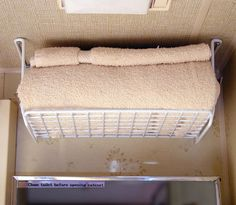 Wire shelf installed upside down in trailer bathroom and used as a towel shelf. So many brilliant storage ideas on this site!