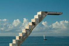 Southern Africa. Mozambique. Ilha de Mocambique. Stone town. Dhows passing abandoned concrete staircase and diving board from abandoned Portuguese swimming pool. Ilha De Mocambique, Mozambique, Southern East Africa.