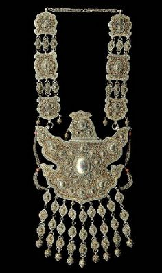 Uzbekistan | Pectoral plate; In bird form, the body hollow with hinged top, worked in fine filigree overall, inlaid with carnelian, turquoise, damascened plaques, and hardstones, with similarly decorated hanging pendants terminating in openwork orbs, with chains emanating from the wings topped with a coral bead, the front gilt and silver on reverse | 19th/20th century. Bukhara | 22,800$ ~ Sold (3/2005)
