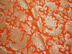 Brocade Fabric, indian brocade, Banaras silk, Silk Benarasi Brocade Fabric. This is a beautiful banarasi blended silk brocade floral design fabric in Orange and Gold. The fabric illustrate damask pattern golden weaving on Orange background.  You can use this fabric to make Dresses, Tops, Blouses, Jackets, Crafting, Clutches or Evening Bags, Embellish your clothes, Pillows, Drapery, Home Décor, Outdoor, Quilting, Sewing, General, Upholstery etc use it for scrap booking projects.  Listing for…