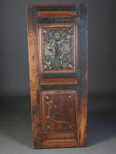 Rosemalt dør med dat. 1785 og 1799. Øvre felt opprinnelig dekorert med en bonde, prest og offiser med innskripsjon. Senere malt blomsterurne over. Nedre felt dekorert med riksløven på en øks.