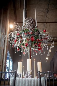 hanging installation with red flowers and pine cones for a winter wedding