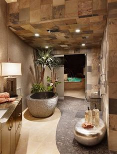 An incredible spa stile bathroom designed by Cornerstone Architects found on houzz.com  Not only is the multicolor slate tile used on the walls, but it carries onto the ceiling as well.  The riverrock soaking tub is even filled by a waterfall from the ceiling!