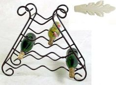 "10 Bottle Wrought Iron Wine Rack (Ivory) (20""H x 23""W x 8""D) by Grace. $116.00. Color: Ivory. 10 Bottle Storage Capacity. Curves Cradle Bottles. Wrought Iron Construction. Size: 20""H x 23""W x 8""D. This 10 Bottle Wine Rack features a sturdy and elegant wrought iron construction, with carefully curved shelves that cradle each bottle of wine or champagne safely. The scrolled feet match the top perfectly and offer stability for a safe wine storage rack. Made in the USA..."