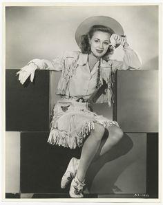 Fringed western wear, 1940s vintage fashion style photo print ad model magazine cowgirl hat vest dress skirt shoes 50s portrait