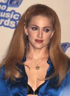 "Madonna's Beauty Evolution -- 1995: At the MTV Video Music Awards -- Winning the ""Best Female Video"" award for ""Take a Bow,"" Madonna goes for a more demure look with medium-blonde hair in a pretty half-up style. Of course, she didn't forget the red lipstick.  