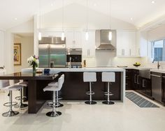 White Kitchen With Modern White Bar Stools. Kitchen With Tube Pendant  Lights Over Brown Kitchen Island With Laminate Countertops