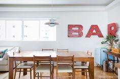 Sala de jantar tem móveis vintage, letras de ferro e um barzinho de apoio.