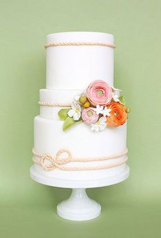 Nautical wedding cake in pastels with delicate rope detailing and pink and orange flowers.