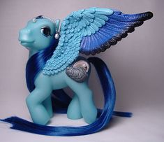 This pegasus was made from a G3 Toys R Us birthstone my little pony who had the jeweled symbol removed. The wings are made of Apoxie Clay over wire and positioned to cover the hole left from the re...