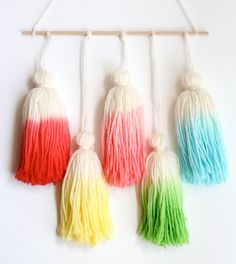 Dip dye yarn tassels for an ombre effect with Kool-Aid. Tutorial by onesheepishgirl.   Affordable and fun wall art.
